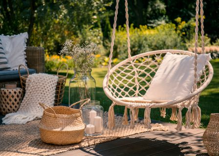 A,Beige,String,Swing,With,A,Pillow,On,A,Patio.